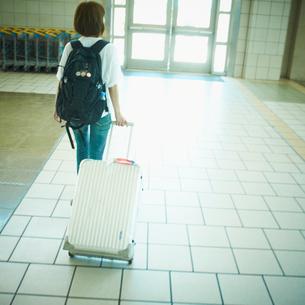 スーツケースを持って歩く女性の写真素材 [FYI02614405]