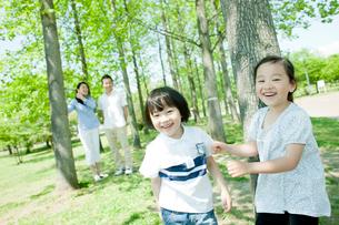 笑顔の子供達と見守る両親の写真素材 [FYI02614424]