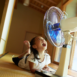扇風機の前で口を開ける女の子の写真素材 [FYI02614959]