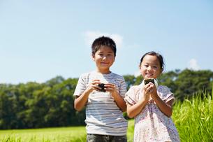 田園でおにぎりを食べる男の子と女の子の写真素材 [FYI02614962]