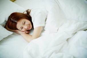 ベッドに横たわる女性の写真素材 [FYI02614986]