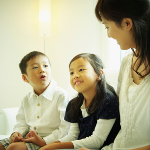 ソファに座る母親と2人の子供の写真素材 [FYI02614988]