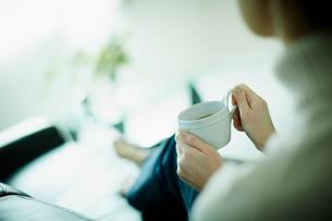 コーヒーカップを持ってソファに座る女性の後姿の写真素材 [FYI02615017]