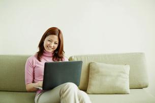 ソファに座りノートパソコンを操作する女性の写真素材 [FYI02615059]