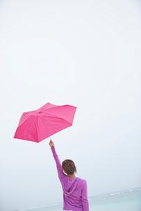 傘を空に掲げる女性と海の写真素材 [FYI02615238]