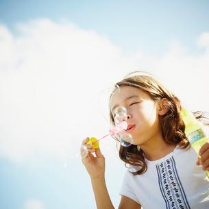 シャボン玉で遊ぶ女の子の写真素材 [FYI02615321]