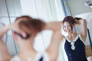 鏡に向かい髪を結う女性の写真素材 [FYI02615347]