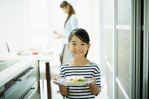 料理を盛った皿を持つ笑顔の女の子の写真素材 [FYI02615572]