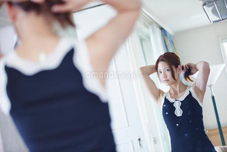 鏡に向かい髪を結う女性の写真素材 [FYI02615602]