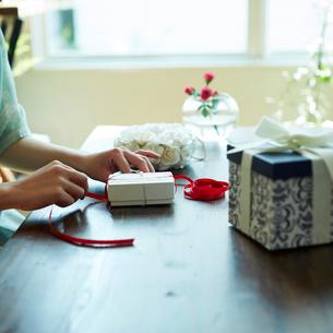 ギフトボックスにリボンをかける女性の手元の写真素材 [FYI02615760]