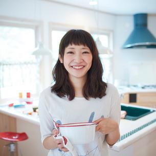鍋を持つ笑顔の若い女性の写真素材 [FYI02615827]