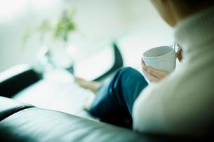 コーヒーカップを持ってソファに座る女性の後姿の写真素材 [FYI02615996]