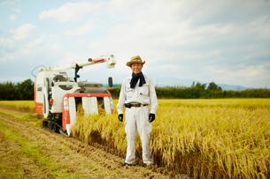 稲田のコンバインと笑顔の農夫の写真素材 [FYI02616054]