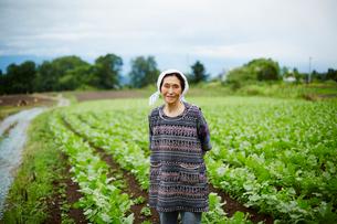 畑に立つ笑顔の農婦の写真素材 [FYI02616091]