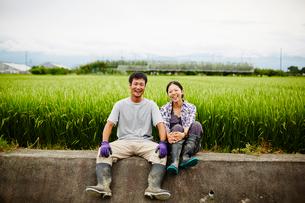 水田と笑顔の農家夫婦の写真素材 [FYI02616097]