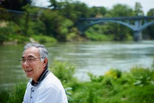 川を眺める笑顔のシニア男性の写真素材 [FYI02616121]
