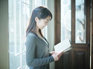 窓辺で本を読む女性の横顔の写真素材 [FYI02616130]