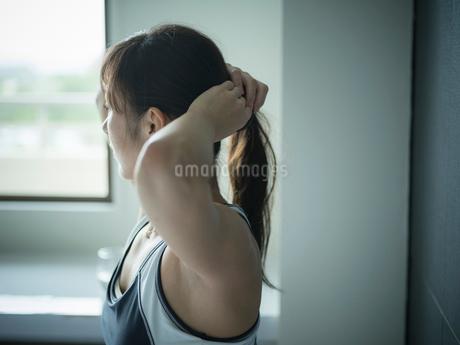 髪を結うトレーニングウェア姿のミドル女性の写真素材 [FYI02616175]