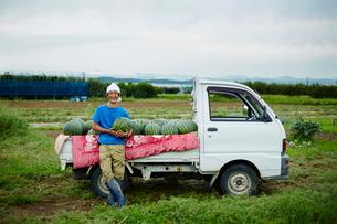 スイカを積んだトラックとスイカを抱える笑顔の農夫の写真素材 [FYI02616197]