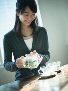 ハーブティーをカップに注ぐ女性の写真素材 [FYI02616201]