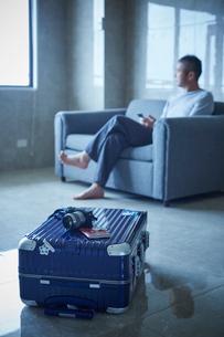 スーツケースとソファに座るミドル男性の写真素材 [FYI02616212]