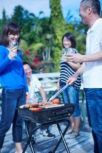 ガーデンパーティーでバーベキューをする2組の夫婦の写真素材 [FYI02616267]