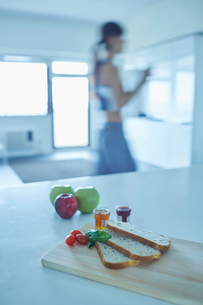 テーブルの上の軽食とトレーニングウェア姿の女性の写真素材 [FYI02616283]