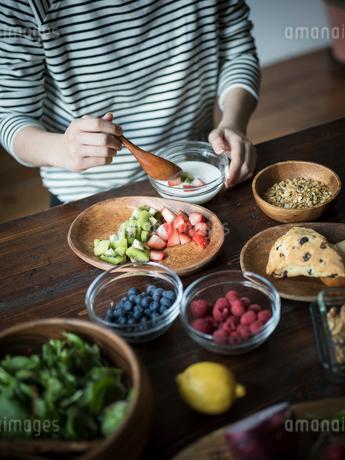 フルーツグラノーラヨーグルトを食べる女性の手元の写真素材 [FYI02616298]