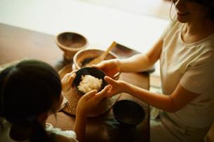 ご飯茶碗を渡す母親と女の子の写真素材 [FYI02616393]