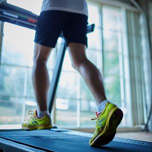ランニングマシーンでトレーニングするシニア男性の写真素材 [FYI02616453]