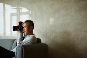 カメラを構えるミドル男性の写真素材 [FYI02616459]