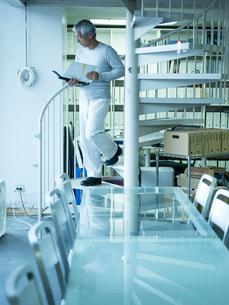 オフィスのらせん階段を下りるシニア男性の写真素材 [FYI02616464]