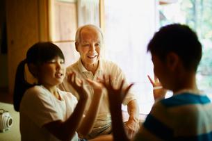 あやとりをする孫たちと笑顔の祖父の写真素材 [FYI02616476]