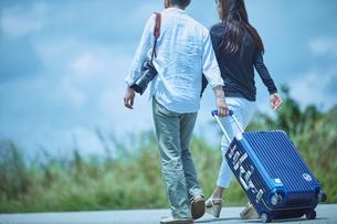 スーツケースをひいて歩くミドル夫婦の写真素材 [FYI02616651]