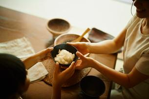 ご飯茶碗を渡す母親と女の子の写真素材 [FYI02616653]