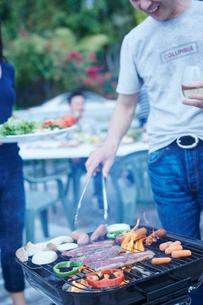 ガーデンパーティーでバーベキューをする夫婦の写真素材 [FYI02616658]