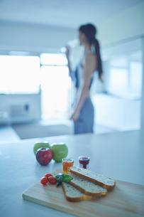 テーブルの上の軽食とトレーニングウェア姿の女性の写真素材 [FYI02616698]
