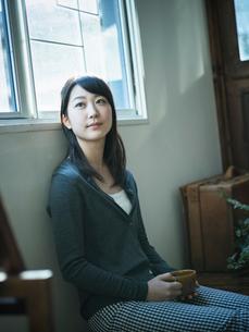 コーヒーカップを持ってくつろぐ女性の写真素材 [FYI02616744]