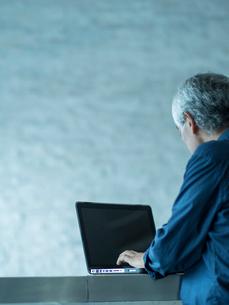 ノートパソコンを操作するシニア男性の写真素材 [FYI02616749]