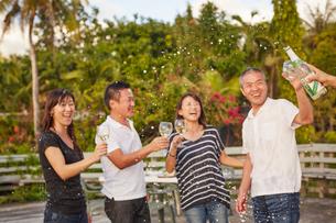シャンパンシャワーを楽しむ2組の夫婦の写真素材 [FYI02616794]