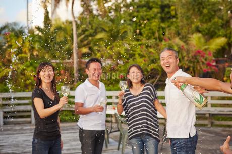 シャンパンシャワーを楽しむ2組の夫婦の写真素材 [FYI02616796]