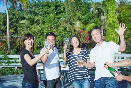 シャンパンシャワーを楽しむ2組の夫婦の写真素材 [FYI02616910]