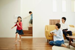 リビングルームで走り回る子供達とくつろぐ両親の写真素材 [FYI02616921]