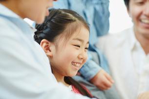 家族に囲まれた笑顔の女の子の写真素材 [FYI02616947]