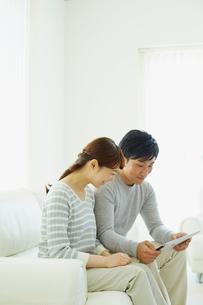 タブレットPCを見る若いカップルの写真素材 [FYI02616948]
