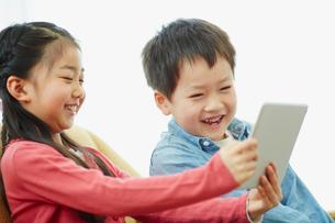 タブレットPCを見る男の子と女の子の写真素材 [FYI02616974]