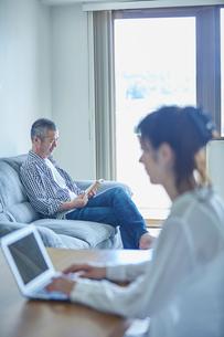 ノートパソコンを操作する女性と読書をする男性の写真素材 [FYI02616975]