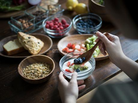 フルーツグラノーラヨーグルトを食べる女性の手元の写真素材 [FYI02617052]