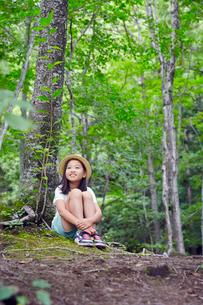 木の根元に座る女の子の写真素材 [FYI02617062]