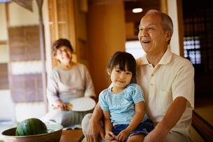 祖父に抱かれる女の子と見守る祖母の写真素材 [FYI02617069]